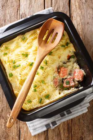 Fish casserole with mashed potatoes and salmon close-up in a baking dish on the table. Vertical top view from above
