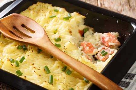Delicious casserole with mashed potatoes, cream, onions and salmon close-up in a baking dish on the table. horizontal
