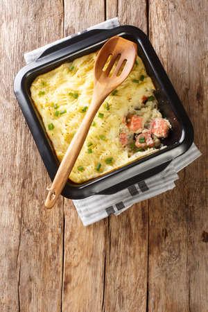 Homemade shepherd salmon pie close-up in a baking dish on the table. vertical top view from above