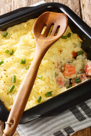 Fish casserole with mashed potatoes and salmon close-up in a baking dish on the table. vertical