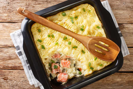 Delicious casserole with mashed potatoes, cream, onions and salmon close-up in a baking dish on the table. horizontal top view from above 免版税图像