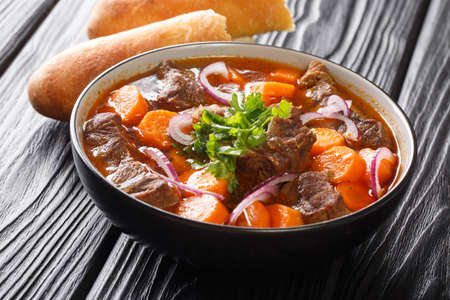 Bo Kho beef ragout in spicy sauce with carrots served with Vietnamese bread close-up in a bowl on the table. horizontal Banque d'images