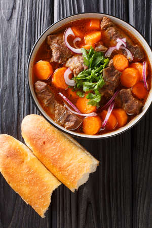 Vietnamese bo kho beef stew is packed with tender, fall-apart braised chunks of beef loaded with herbs, aromatics and a delicious broth closeup in bowl. Vertical top view from above