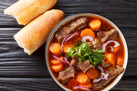 Bo Kho beef ragout in spicy sauce with carrots served with Vietnamese bread close-up in a bowl on the table. Horizontal top view from above 免版税图像