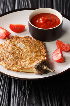 Tortang talong is a Filipino omelette made by pan frying grilled whole eggplants dipped in an egg mixture close-up in a plate on the table. Vertical