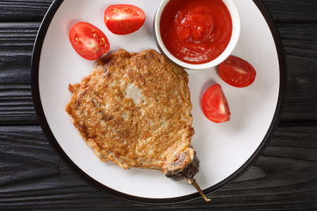 Eggplant Omelet Tortang Talong served with ketchup close-up on a plate on the table. horizontal top view from above