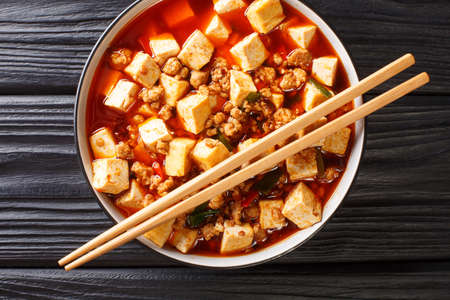 Tender mapo tofu cooked in an aromatic and spicy sauce, accompanied by minced meat closeup in the plate on the table. Horizontal top view from above 免版税图像