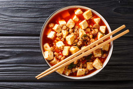 Mapo tofu is a famous Sichuan dish consisting of tofu, minced pork, hot sauce closeup in the plate on the table. Horizontal top view from above