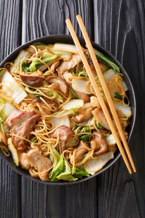 Braised Glass Noodles with Pork & Napa is a traditional Chinese dish close-up in a plate on the table. Vertical top view from above