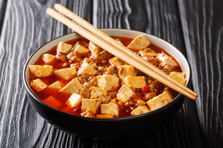 Chinese Mapo Tofu is fried Sichuan pork and tofu in a hot sauce close-up in a bowl on the table. horizontal 免版税图像