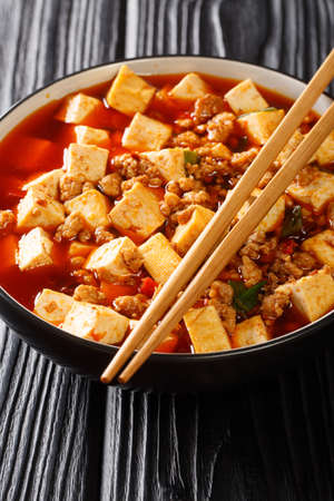 Authentic Chinese style mapo tofu is one of the branding dishes of Szechuan cuisine closeup in the plate on the table. vertical