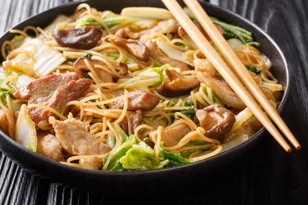 Asian noodles with fried pork belly, mushrooms and napa cabbage in soy sauce close-up in a plate on the table. horizontal