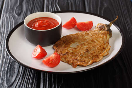 Eggplant Omelette or Tortang Talong is a Filipino dish consists simply of eggplant that is coated in egg and then fried close-up on a plate on the table. Horizontal