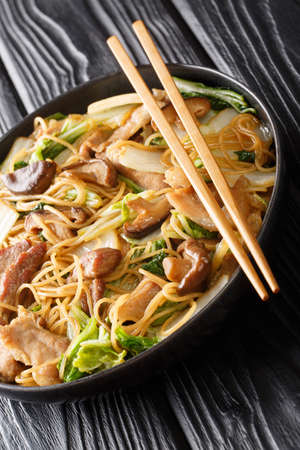 Braised Glass Noodles with Pork & Napa is a traditional Chinese dish close-up in a plate on the table. Vertical