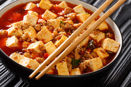 Tender mapo tofu cooked in an aromatic and spicy sauce, accompanied by minced meat closeup in the plate on the table. Horizontal