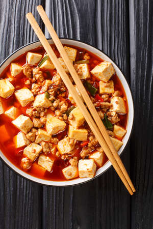 Authentic Chinese style mapo tofu is one of the branding dishes of Szechuan cuisine closeup in the plate on the table. Vertical top view from above