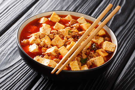 Mapo tofu is a famous Sichuan dish consisting of tofu, minced pork, hot sauce closeup in the plate on the table. Horizontal