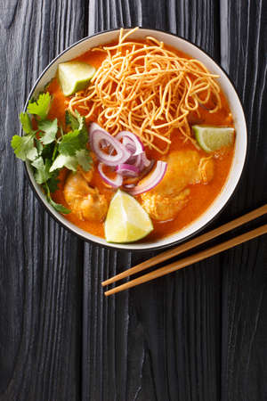 Khao Soi is a popular coconut curry noodles soup with chicken closeup in the bowl on the table. Vertical top view from above
