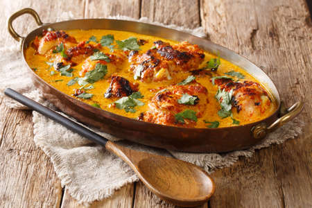 Kuku Paka is a spiced chicken and coconut curry dish that is full of exotic flavors closeup in the pan on the table. Horizontal Banco de Imagens