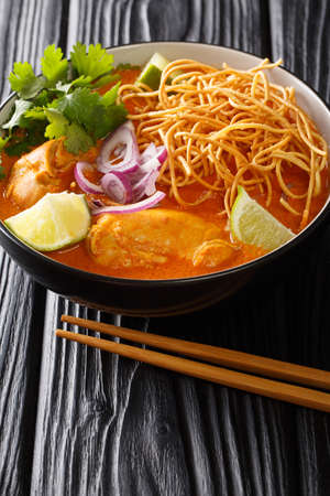 Khao Soi is a popular coconut curry noodles soup with chicken closeup in the bowl on the table. Vertical 免版税图像