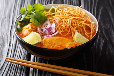 Khao Soi is a creamy, slightly spicy yellow curry noodle dish found in Northern Thailand closeup in the bowl on the table. Horizontal Banco de Imagens