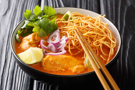 Chicken khao soi thai coconut curry noodle soup closeup in the bowl on the table. Horizontal