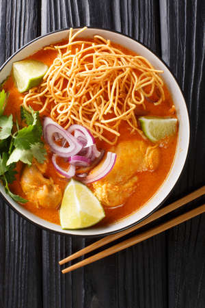 Khao soi or khao soy is a Chin Haw dish served widely in Myanmar Laos and northern Thailand closeup in the bowl on the table. Vertical top view from above 免版税图像