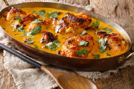 Kenyan Kuku Paka is a chicken roasted over charcoal and then cooked in a coconut curry closeup in the pan on the table. Horizontal Stock Photo