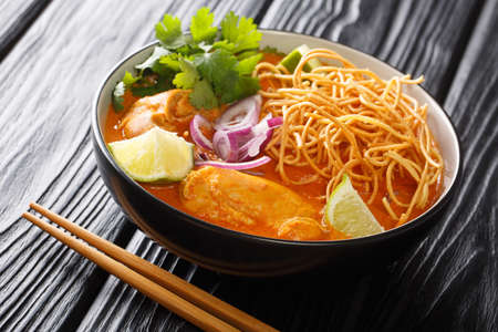 Tasty Khao soi, a noodle soup originating in Thailand, is loaded chicken, shallots, and garlic in a coconut milk-based broth closeup in the bowl on the table. Horizontal Banco de Imagens