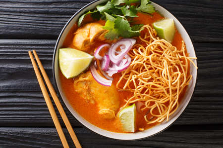 Coconut curry soup with chicken, fried noodles and spices. Thai style. close-up horizontal top view from above 免版税图像
