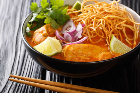 Coconut curry soup with chicken, fried noodles and spices. Thai style. close-up horizontal 免版税图像