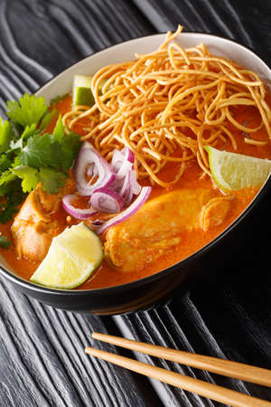 Khao soi or khao soy is a Chin Haw dish served widely in Myanmar Laos and northern Thailand closeup in the bowl on the table. Vertical