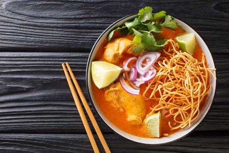 Tasty Khao soi, a noodle soup originating in Thailand, is loaded chicken, shallots, and garlic in a coconut milk-based broth closeup in the bowl on the table. Horizontal top view from above