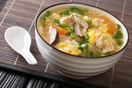 Fragrant Japanese thick rice soup Zosui with egg, mushrooms, vegetables close-up in a bowl on the table. horizontal