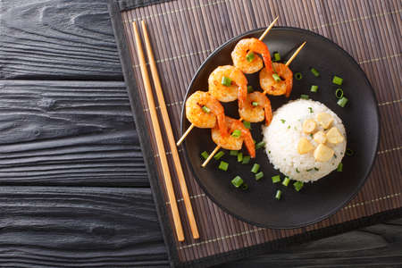 Asian garlic fried rice served with shrimps on skewers close-up in a plate on the table. horizontal top view from above