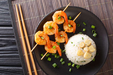 Delicious Japanese garlic fried rice served with shrimp kebabs close-up in a plate on the table. horizontal top view from above