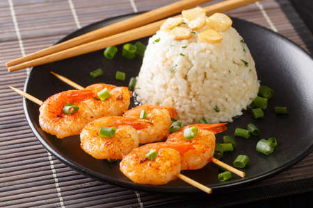 Butter garlic rice with fried shrimps on skewers close-up in a plate on the table. horizontal Banco de Imagens