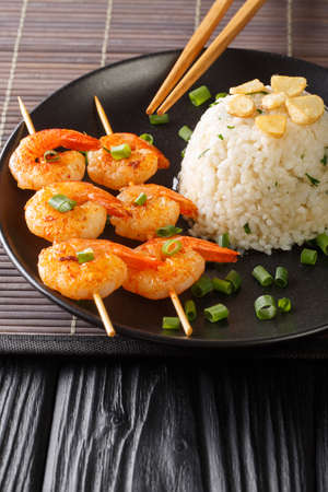 Garlicky and buttery, this simple Japanese Garlic Fried Rice topped with garlic chips with fried shrimps close-up in a plate on the table. Vertical Banco de Imagens