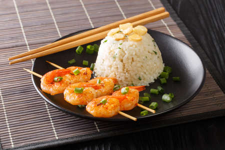 Japanese traditional food garlic rice with fried shrimp on skewers close-up in a plate on the table. horizontal