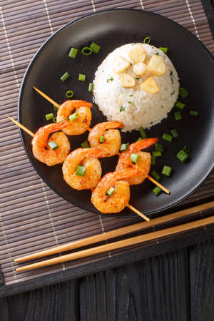 Japanese garlic rice served with fried shrimps close-up in a plate on the table. Vertical top view from above