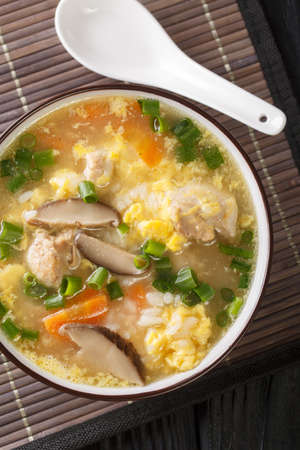 Zosui is a comforting Japanese rice soup cooked in a savory dashi broth with vegetables, eggs, mushrooms, and chicken close-up in a bowl on the table. Vertical top view from above
