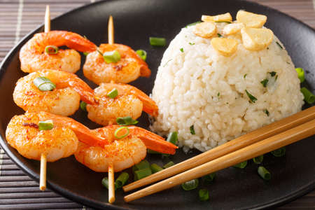 Japanese garlic rice served with fried shrimps close-up in a plate on the table. horizontal