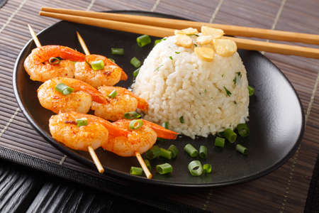 Asian garlic fried rice served with shrimps on skewers close-up in a plate on the table. horizontal Banco de Imagens