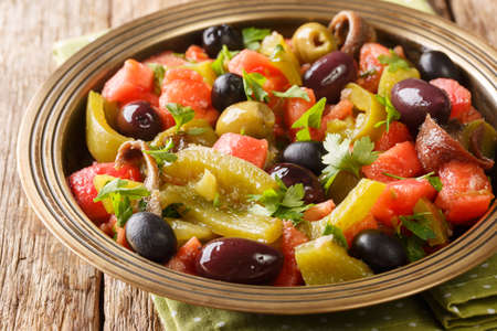 Delicious salad of tomatoes and green peppers Chlada felfel with anchovies and olives close-up in a bowl on the table. horizontal Imagens