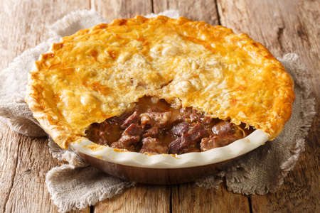English homemade ale beef steak pie with crispy puff pastry close-up in a baking dish on the table. horizontal