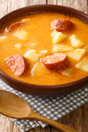 Hungarian Krumplileves potato soup with sausages close-up in a plate on the table. Vertical Standard-Bild