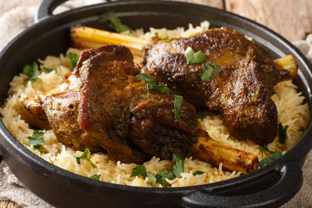 Haneeth is a slow roasted lamb dish from Yemen served on a plate of rice closeup on the table. horizontal
