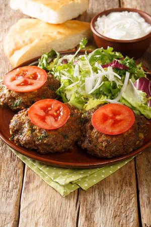 Chapli Kebab或Kabab切碎的Kebab由磨碎的羊肉和各种香料做成肉饼的形状在盘子上的特写镜头。垂直