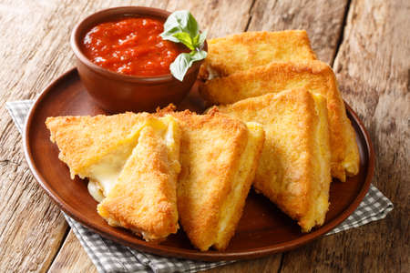 Mozzarella in Carrozza sandwich gets an extra dose of richness from a creamy egg bath and is coated in breadcrumbs for extra crunch closeup in the plate on the table. horizontal