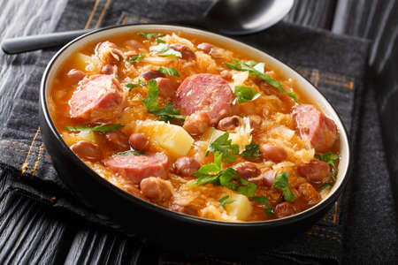 Portion of Jota sauerkraut with borlotti beans, potatoes and sausages close-up in a bowl on the table. horizontal